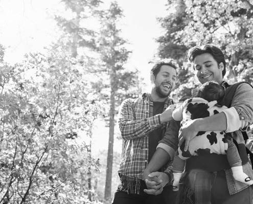 Gay men hold baby - Intended parents - LGBTQ+ surrogacy services